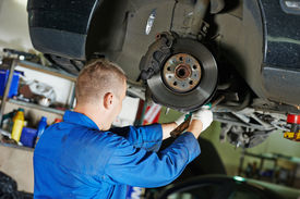 picture of levers  - car mechanic worker repairing suspension of lifted automobile at auto repair garage shop station - JPG