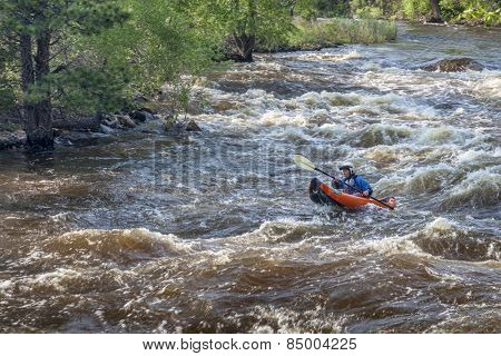 FORT COLLINS, CO, USA - JUNE 4, 2011: Female kayaker paddling inflatable boat over Maddog Rapid on Cache la Poudre River west of Fort Collins, Colorado as snow pack in the high country begins to melt.