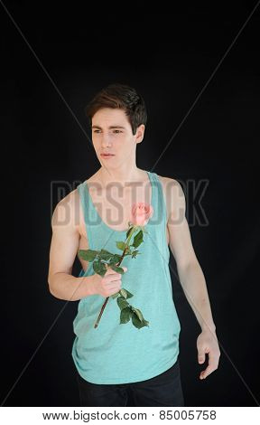 Close-up of young muscular man with perfect body holding pink rose