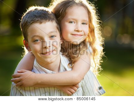 Children outdoors. Happy boy and girl embracing