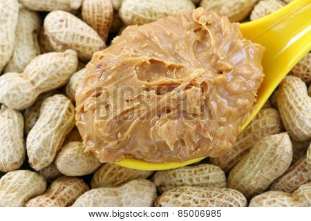 A spoon of creamy crunchy peanut butter on peanuts