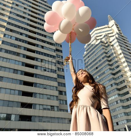 Beautiful young girl holding colored balloons over high-rise building. Urban teenage background. Toned.