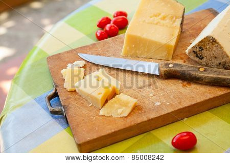 Pecorino sardo cheese slices on wooden board with knife