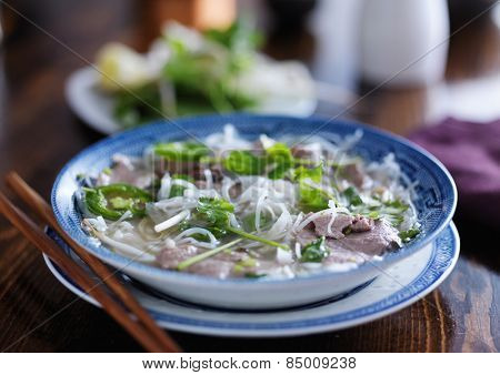 pho in a bowl with beef slices and noodles