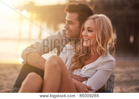 two lovers at santa monica beach holding each other with lens flare and warm image tone