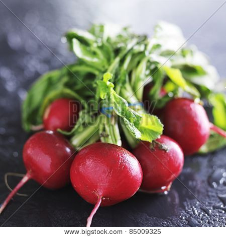 bunch of fresh radishes on slate surface