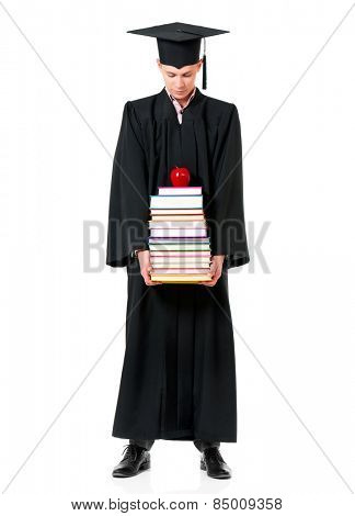 Handsome graduate guy student in mantle with books and apple, isolated on white background