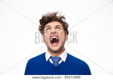 Angry young man shouting and looking up at copyspace