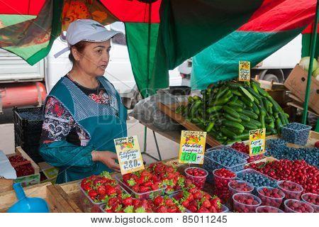 The Saleswoman Selling Berries In Vegetable Fair