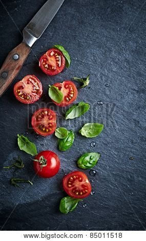 Halved cherry tomatoes and basil leaves on a black slate