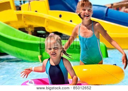 Child on water slide at aquapark. Blue bikini.