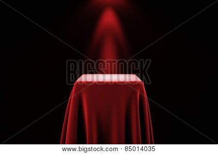 Presentation pedestal covered with a red silk cloth in front of a wall illuminated by a spot light
