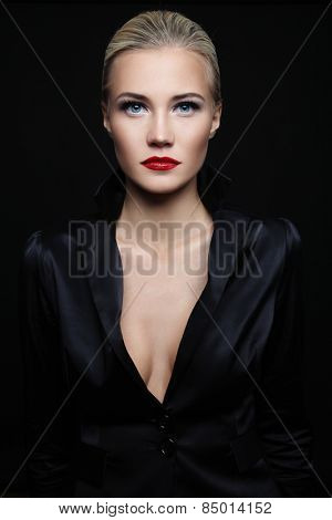 Young beautiful blond glamorous woman in black silky jacket over dark background