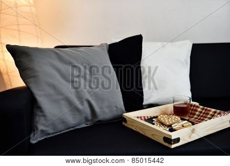 Pillows and tray with cookies on a sofa
