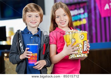 Portrait of smiling siblings holding popcorn tub and cold drink at cinema