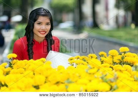 Attractive young Vietnamese woman smiling happily at the camera over a display of yellow flowers in an urban street