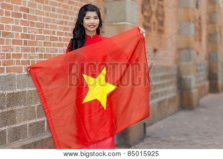 Pretty young Vietnamese woman with a lovely friendly smile holding up a the national flag of Vietnam as she stands in an urban street against a brick wall