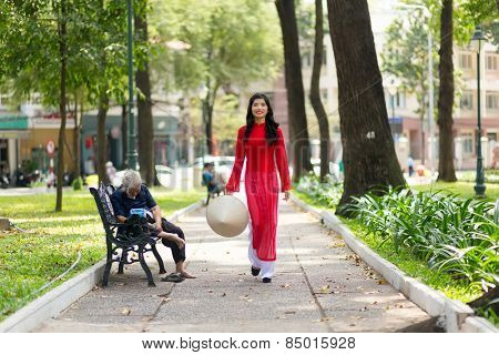 Elegant young Vietnamese woman wearing a traditional red dress walking through a public park past a bench with a person sitting on it