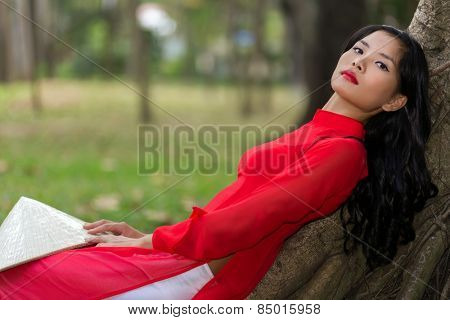 Slender young Vietnamese woman relaxing in a park leaning back against the aerial roots of a tree in her traditional red outfit looking at the camera with a serious expression