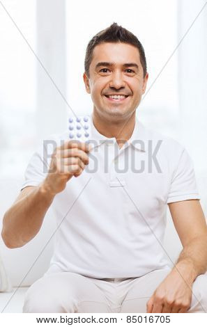 people, medication, medicine and health care concept - happy man showing pack of pills at home