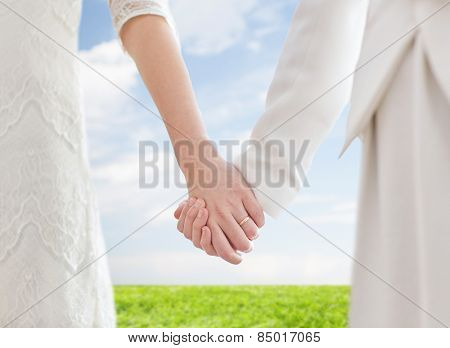 people, homosexuality, same-sex marriage and love concept - close up of happy married lesbian couple holding hands with wedding ring on over blue sky and grass background