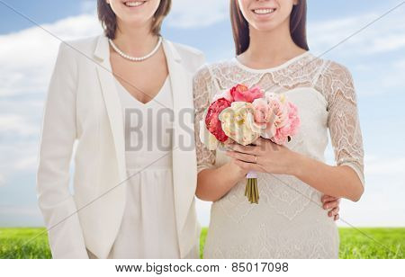 people, homosexuality, same-sex marriage, honeymoon and love concept - close up of happy married lesbian couple with flower bunch over blue sky and grass background