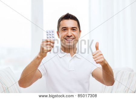 people, medication, medicine and health care concept - happy man showing thumbs up and holding pack of pills at home