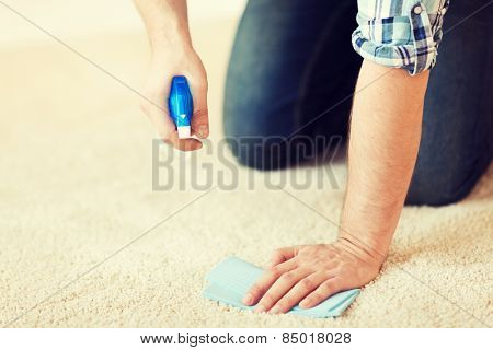 cleaning and home concept - close up of male cleaning stain on carpet with cloth