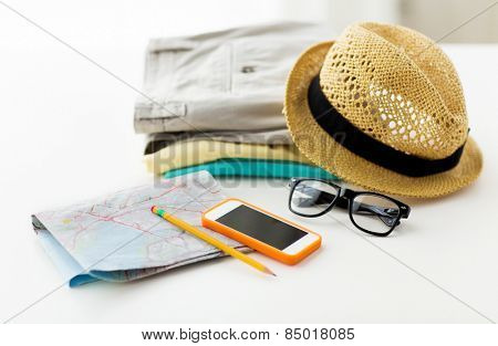 travel, summer vacation, tourism and objects concept - close up of folded clothes, smartphone and touristic map on table at home