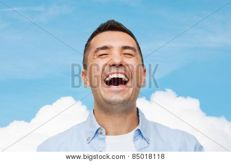 happiness, emotions and people concept - laughing man over blue sky and cloud background