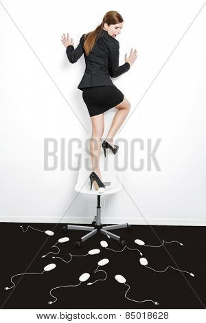 Business concept with a beautiful woman in the office being attacked by mice