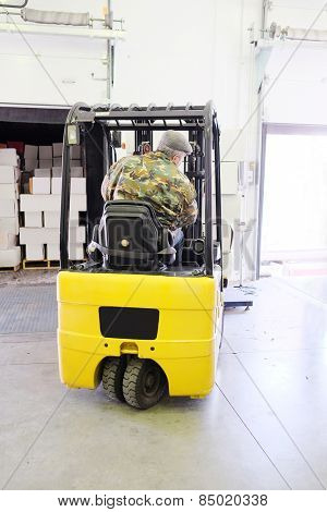 Worker driver stacking boxes by forklift stacker loader