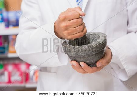 Pharmacist in lab coat mixing a medicine in the pharmacy