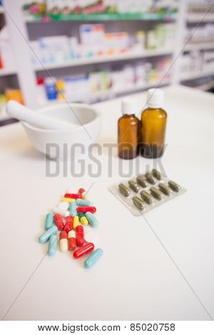 Close up of medicines and jar near a mortar in the pharmacy