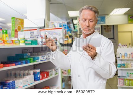 Concentrated pharmacist reading prescription in the pharmacy