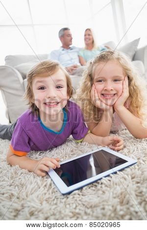 Happy siblings with digital tablet lying on rug while parents sitting on sofa at home