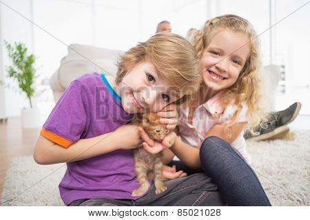 Portrait of cute brother and sister with kitten at home