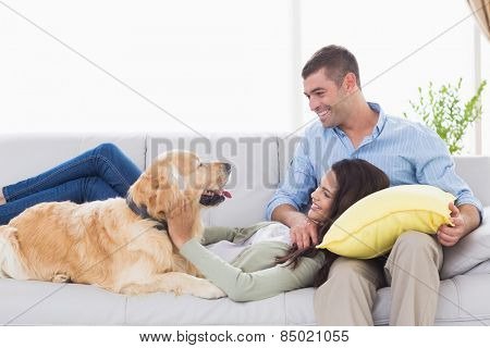 Happy couple with dog on sofa at home