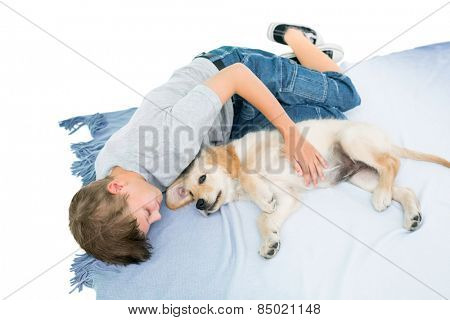 High angle view of boy lying with puppy on blanket over white background