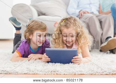 Happy brother and sister using digital tablet while lying on rug at home