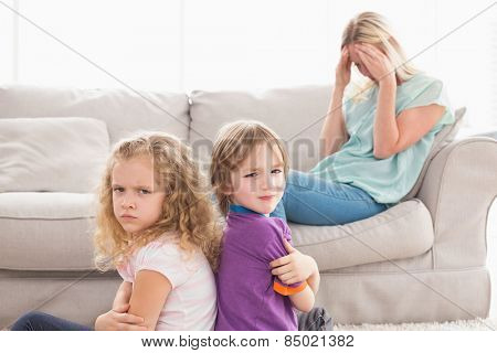 Portrait of angry siblings sitting arms crossed with sad mother on sofa at home