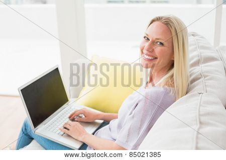 Side view of smiling woman on sofa using laptop in living room