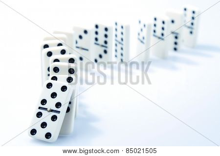 Dominoes on plain background, about to fall