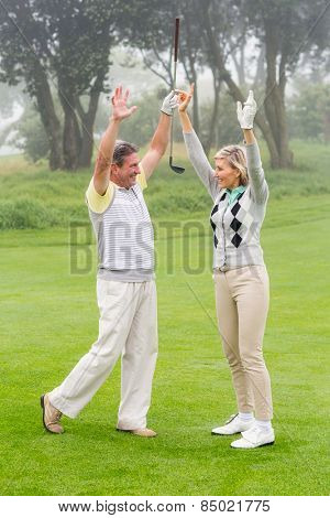 Excited golfing couple cheering on a foggy day at the golf course