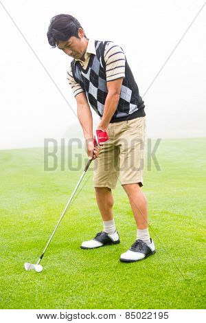 Concentrating golfer lining up his shot at the golf course