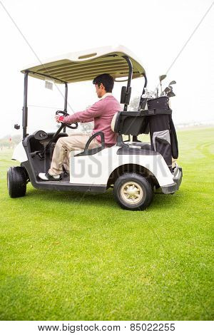 Golfer driving in his golf buggy in golf course