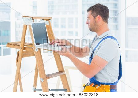 Side view of handyman using laptop by step ladder in bright office