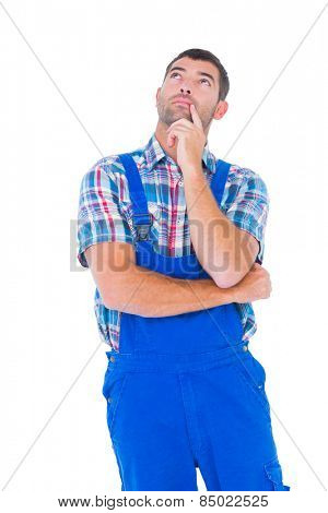 Thoughtful handyman in coveralls looking up on white background