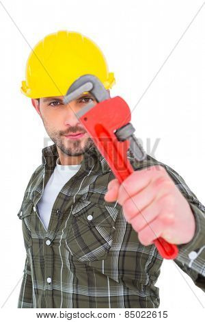 Manual worker looking through monkey wrench on white background