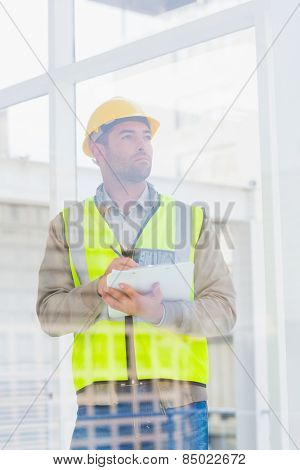 Thoughtful male architect in reflective clothing writing on clipboard at office